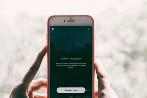 person's hands holding an iphone displaying a live on instagram notification screen