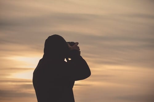 photographer looking through viewfinder of camera at sunset