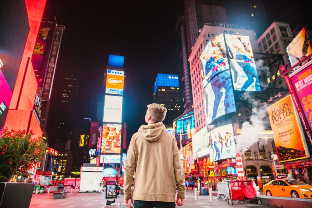 Young man looks up at Times Square signage